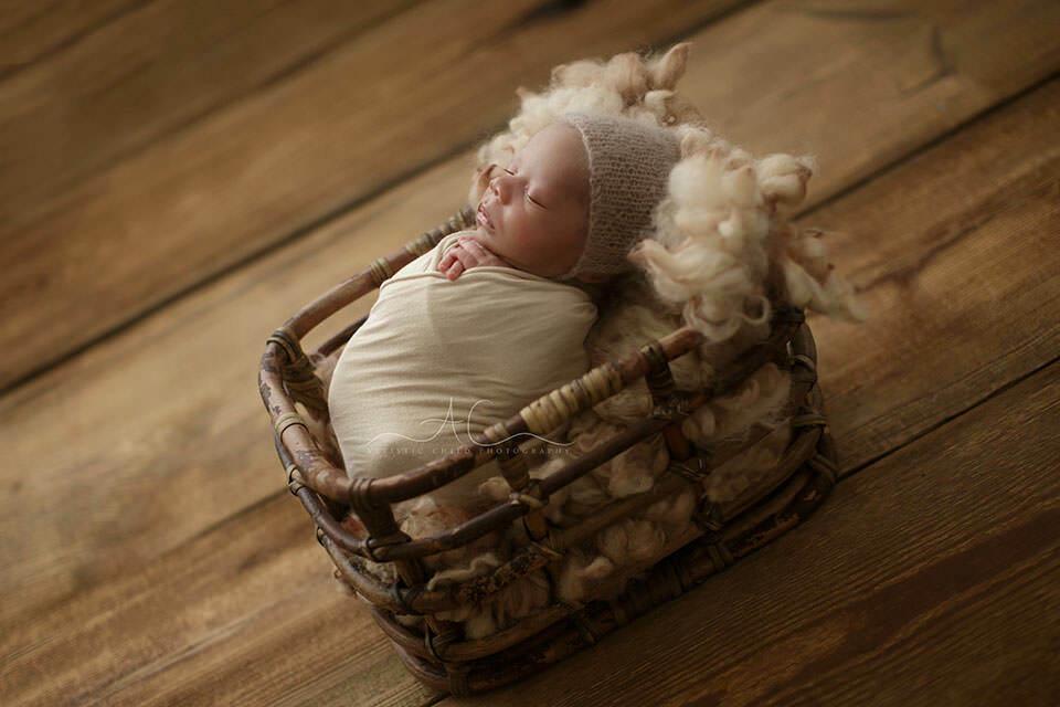 a backlit portrait of a newborn boy sleeping in a bamboo basket | London