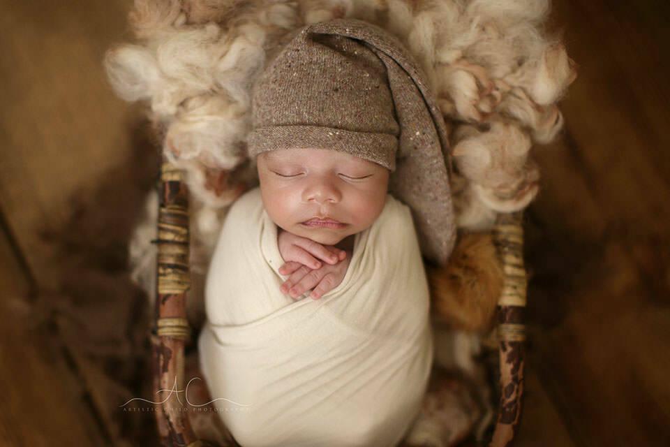 a close up portrait of a newborn baby boy wearing a brown sleepy hat  | London