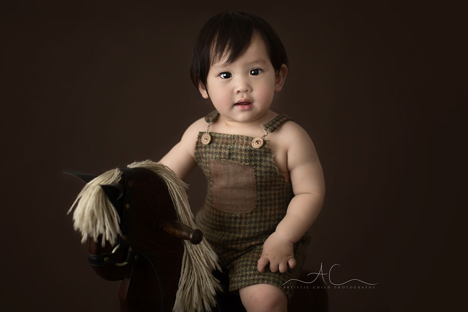 a close up portrait of a 1 year old boy sitting on an old rocking horse   Bromley