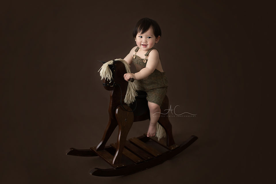 1 year old boy sits on an old wooden rocking horse during the professional photoshoot in Bromley  London