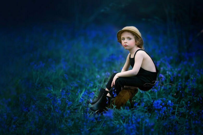 Best Bluebells London Children Photos | portrait of a 4 year old boy sitting on a leather steps in the middle of bluebells