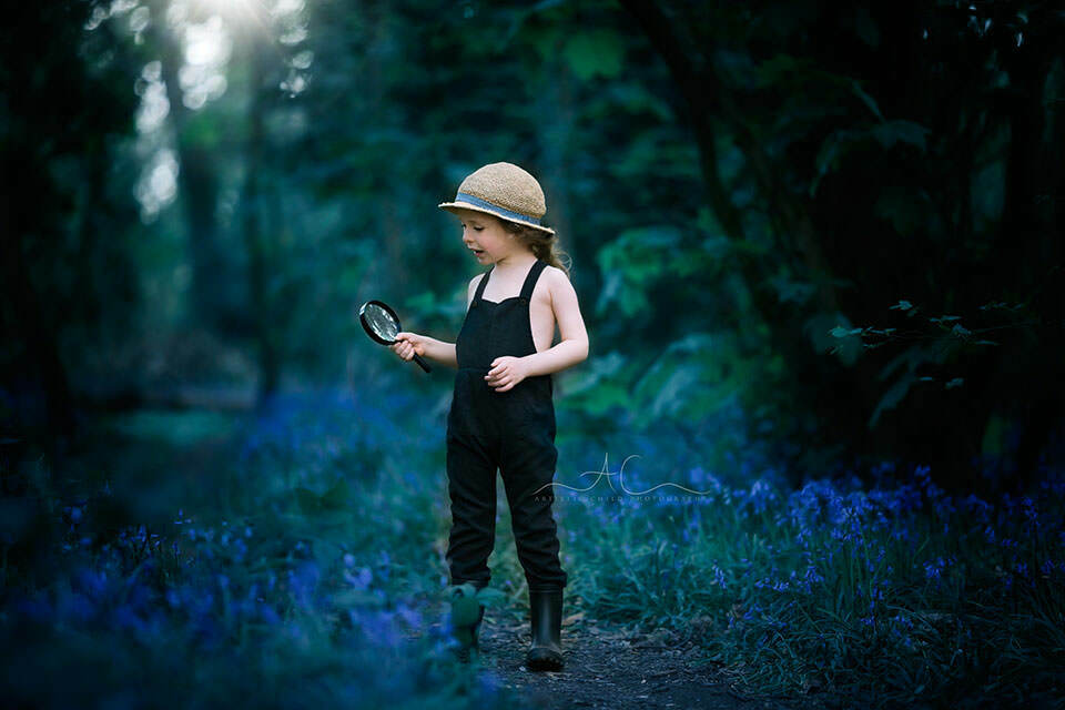 Best Bluebells London Children Photos | 4 year old boy plays with magnifying glass while admiring bluebell flowers