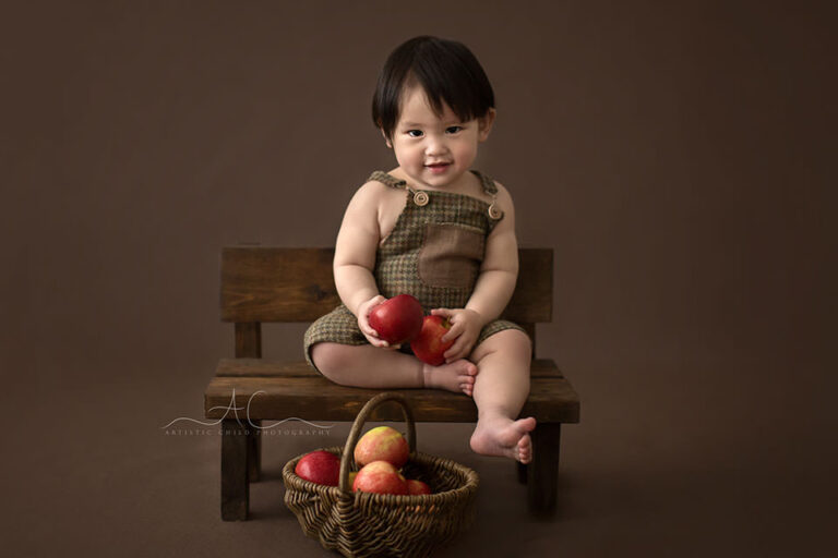 Bromley Child Photos | portrait of a 1 year old boy sitting on a wooden bench
