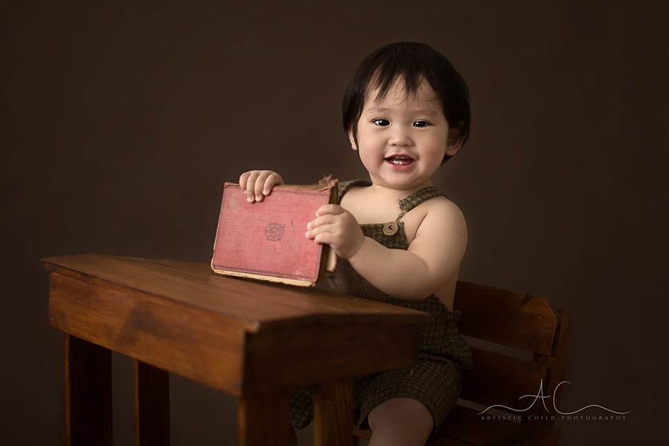 Bromley Child Photos   portrait of a 1 year old toddler boy playing with an old red book