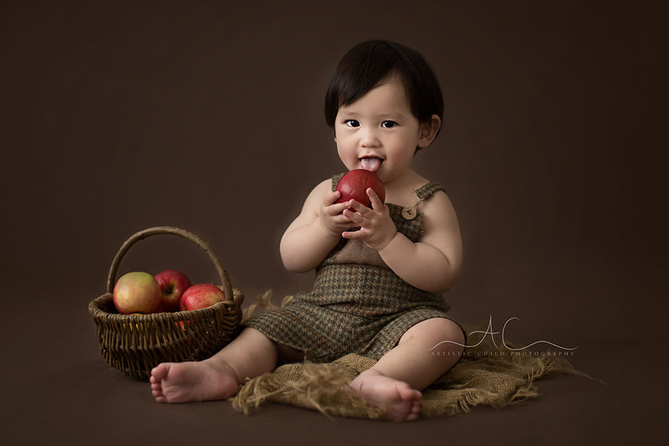 Bromley Child Photos   professional portrait of a 1 year old boy playing with apples during the photo session