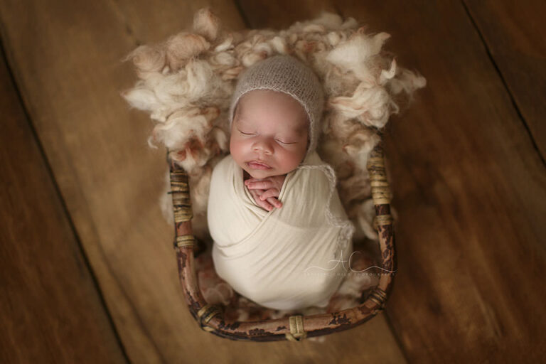 Top London Newborn Photo Session | photo of a newborn baby boy sleeping in a bamboo basket