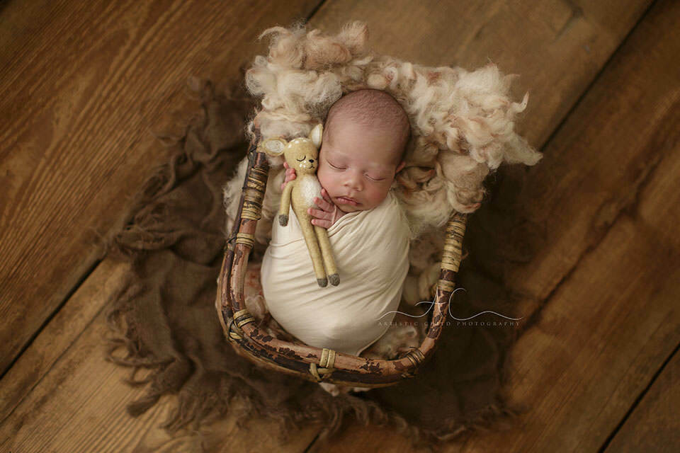 Top London Newborn Photo Session | newborn baby boy holds a toy during a professional photo session