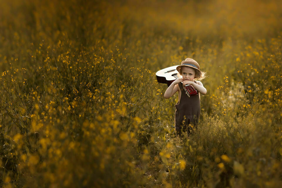 portrait of a 4 year old boy walking through the field with a guitar | London