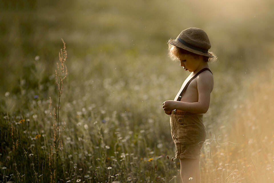 a backlit portrait of 4 year old boy in a straw hat | London