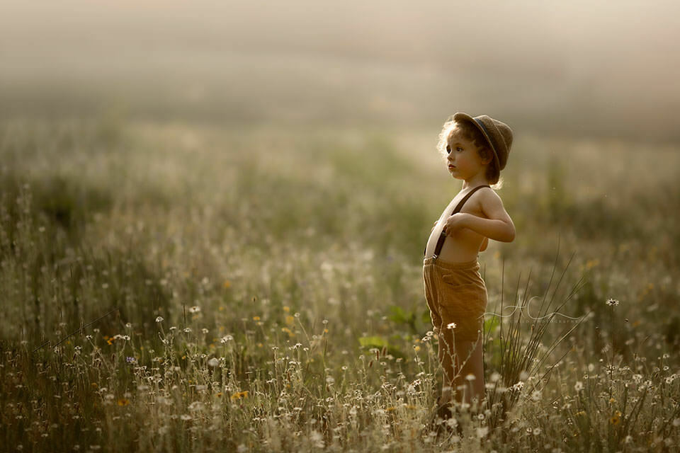 4 year old boy dressed in shorts with braces and straw hat stands in the middle of wildflowe field and contemplates the beauty of the nature   London