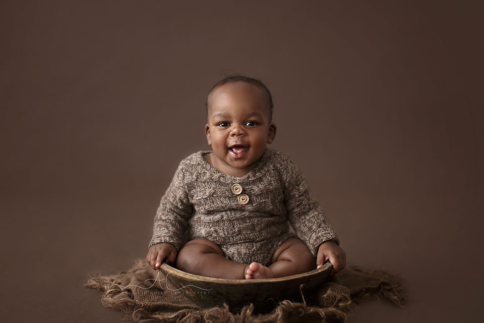 7 months old baby boy sits in a bowl and laughs | South East London