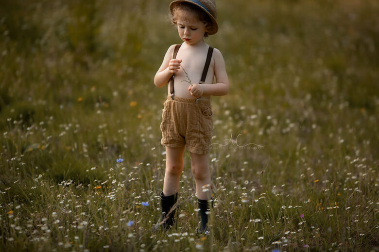 Beautiful London Child Photography in Wildlower Field | portrait of a 4 year old boy wearing a straw hat and looking at the small wildflower