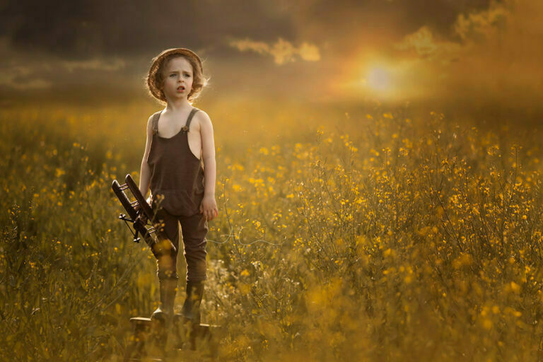 Beautiful London Children Photography in Rapeseed Field | 4 year old boy stands on the wooden step ladder and holds an aeroplane while gazing ahead during the sunset in a rapeseed field