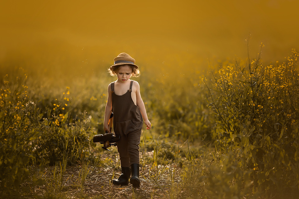 Beautiful London Children Photography in Rapeseed Field | 4 year old boy walks through a rapeseed field with an aeroplane in his hand