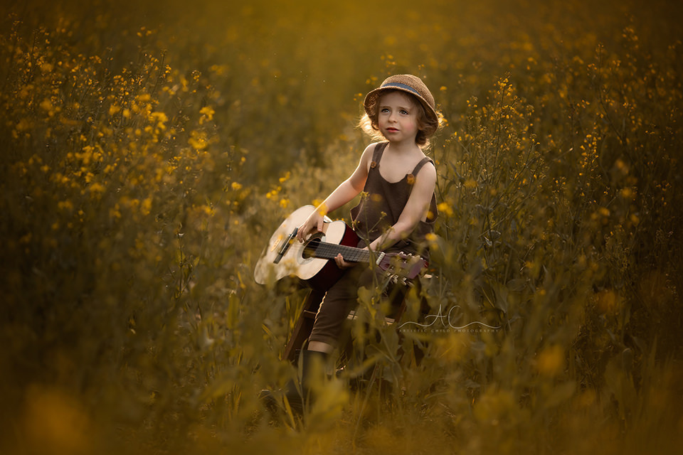 Beautiful London Children Photography in Rapeseed Field | 4 year old boy plays the guitar in a rapeseed field at a golden hour