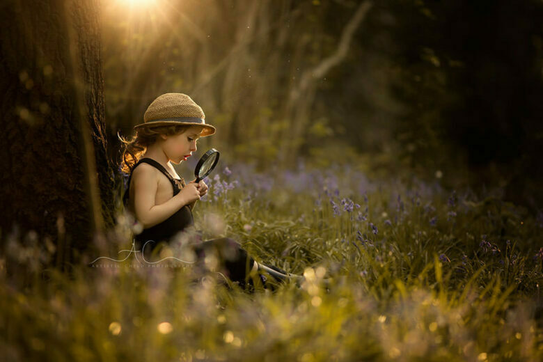 Best Spring London Children Photoshoot | backlit portrait of a 4 year old boy sitting under the tree and playing with magnifying glass