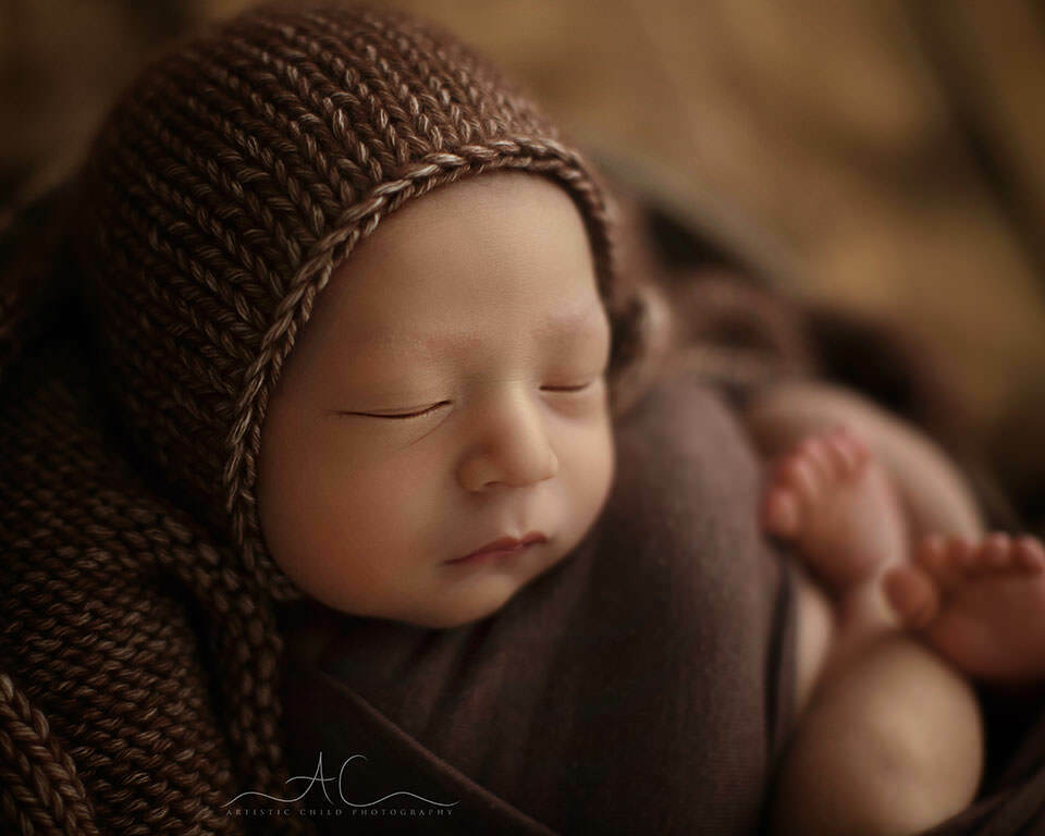 a close up portrait of a newborn baby boy wearing a brown hand knitted hat | Bromley