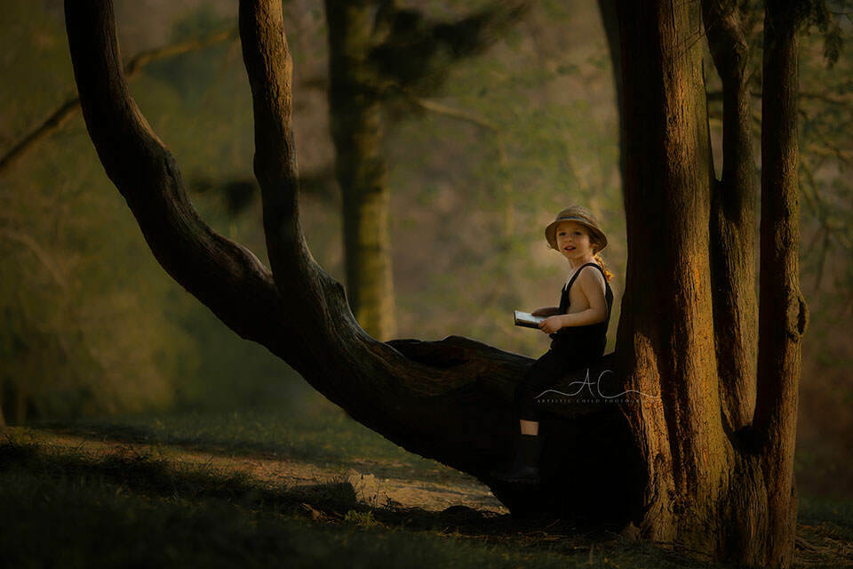 photo of a 4 year old boy stitting on a tree with a book and smiling | London