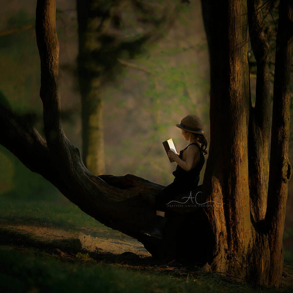 Professional London Children Photos | portrait of a boy sitting on a tree and reading a book