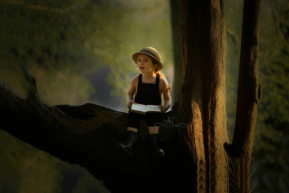 Professional London Children Photos | 4 year old boy sits high on a tree bench with a book