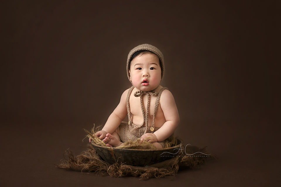portrait of a 7 months old baby boy sitting in a wooden bowl during a professional photo session | South East London