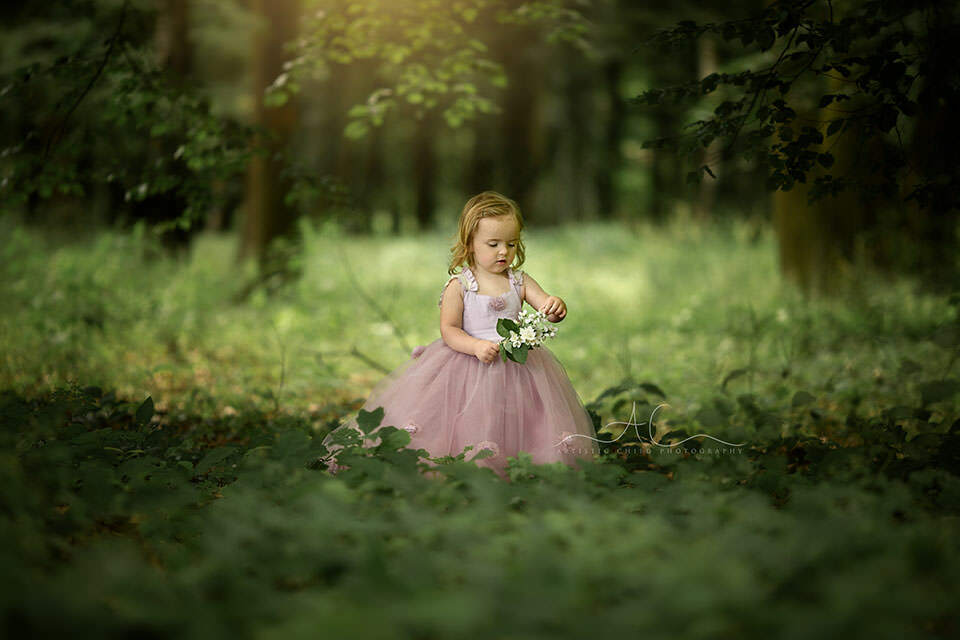 3 year old girl dresses as a princes plays with bunch od flowers in London park
