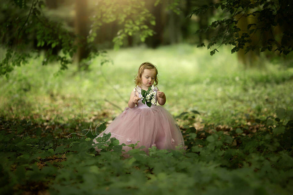 3 years old girl wears pink pincess dress during a professional photoshoot in London park