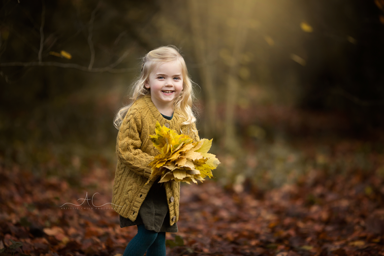 Autumn Mini Photography Sessions London 2020   portrait of a smiley girl with the bunch of autumn leaves