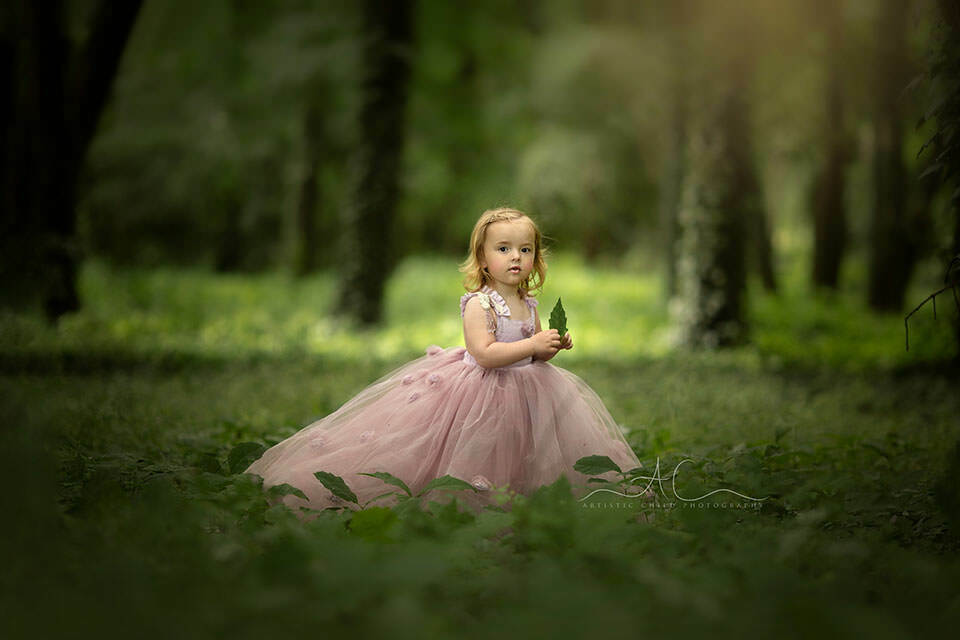 Princess Photo Session in London | an outdoor portrit of a 3 year old girl wearing a pink pricess dress and holding a green leaf in her hands