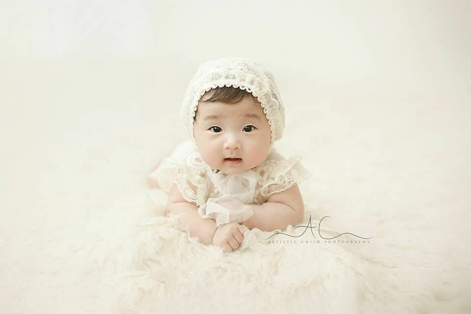 portrait of a 100 days old baby girl wearing a beautiful lace bonnet | London