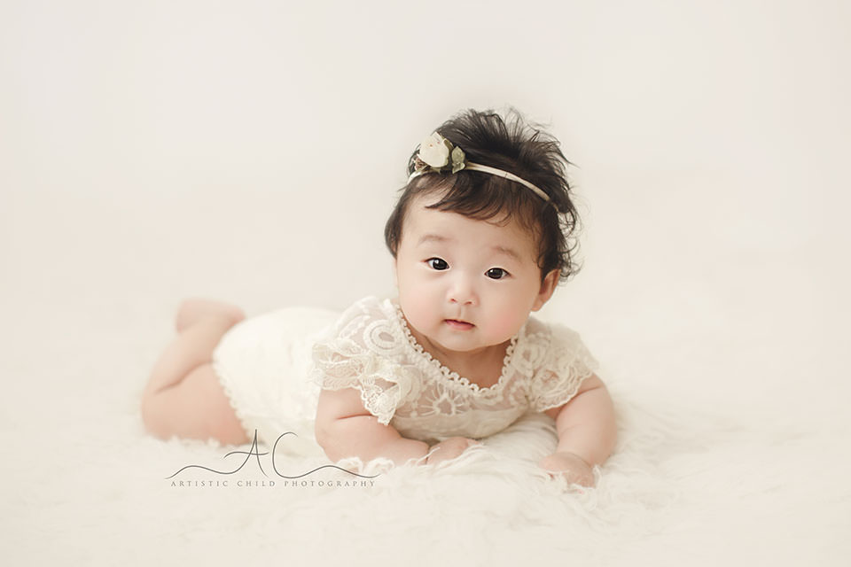 portrait of a 3 months old baby girl wearing a beautiful white flower tieback during a professional photoshoot | London