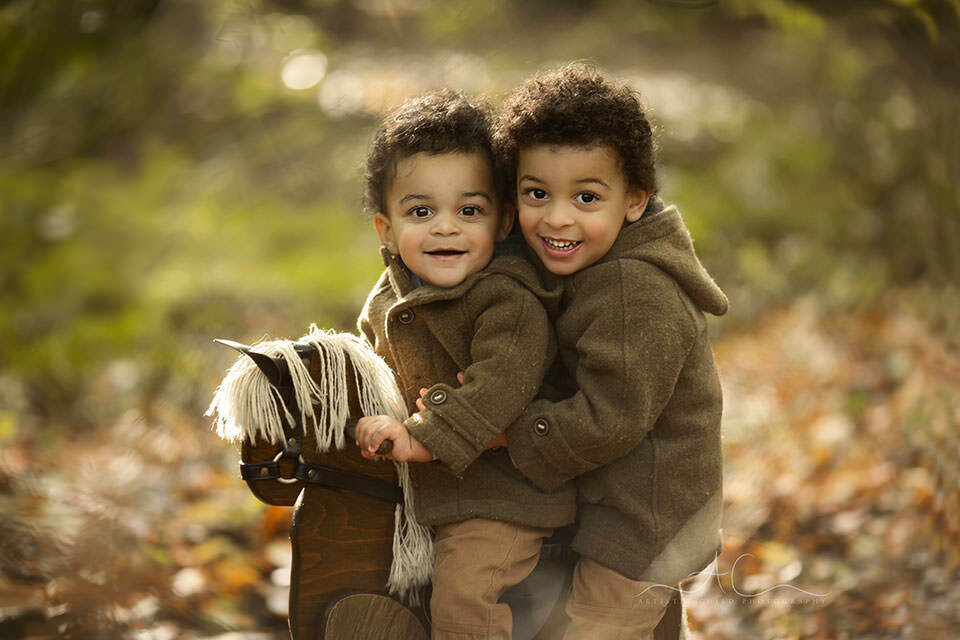 portrait of siblings on a rocking horse in the park during autumn season | Bromley