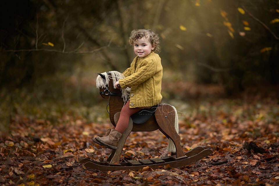 beautiful classic portrait of a 2 year old girl taken during a professional autumnal photo session in London