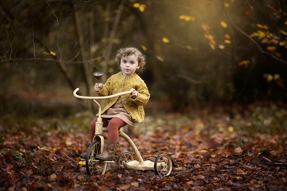 2 years old playing with a bell wile riding on an old bike during a professional autumnal photo session in London