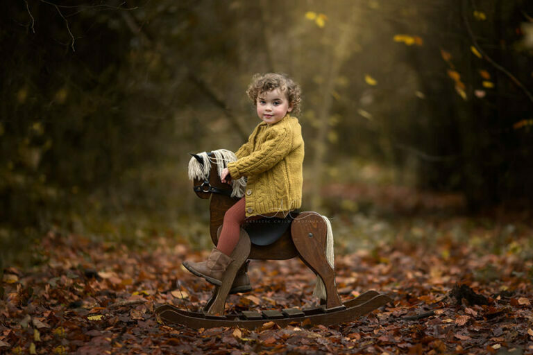 Autumn London Toddler Photo Session | beautiful portrait of a 2 years old girl on a rocking horse taken in London park during autumn season