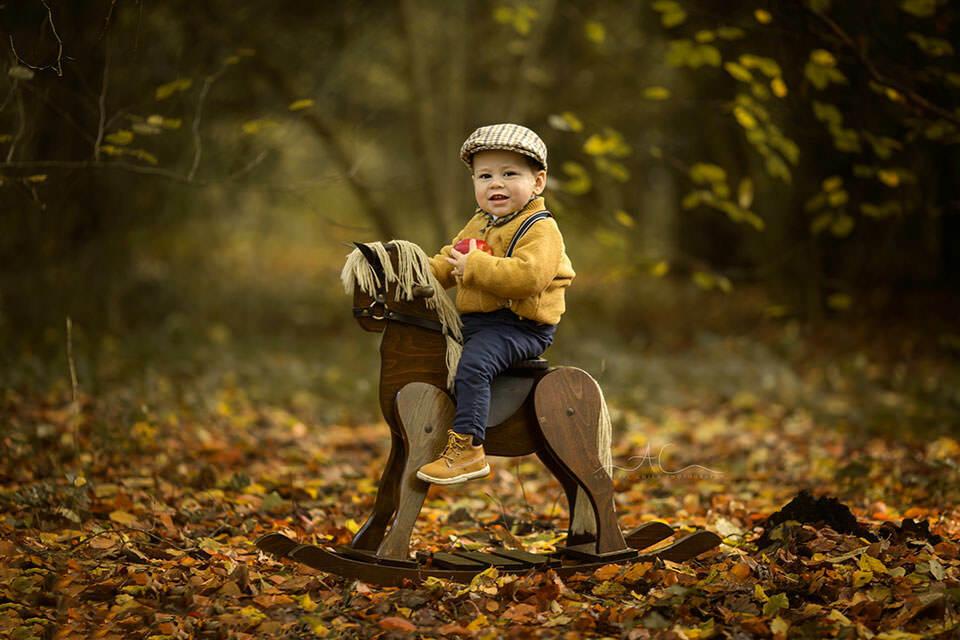 Autumn South East London Toddler Photoshoot | toddler boy smiles while having fun on a rocking horse during autumn mini photo session