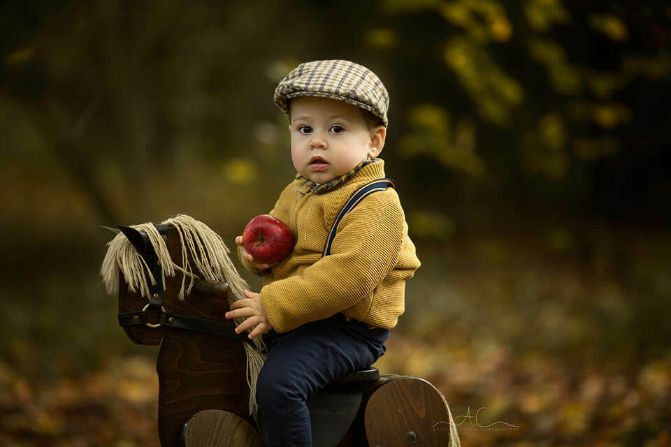 Autumn South East London Toddler Photoshoot | a close up portrait of a toddler boy wearing a flat cap during autumn mini photoshoot