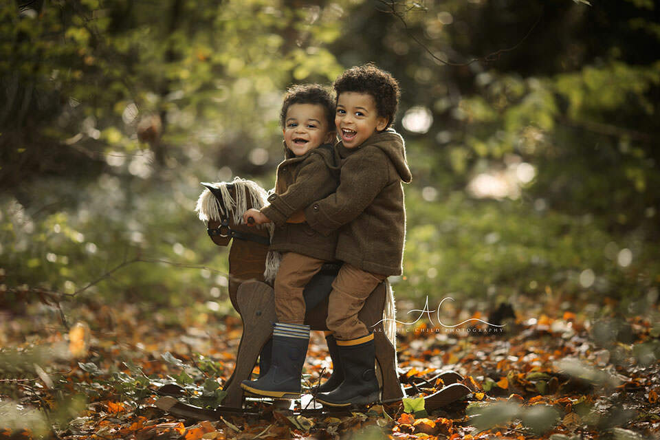 Bromley Autumn Sibling Photography | brothers laughing whole playing on a rocking horse in the park during autumn mini photoshoot