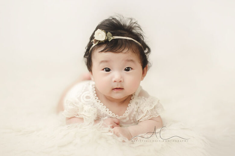 London 100 Days Old Baby Photos | portrait of a 3 months old baby girl wearing a beautiful white lace outfit