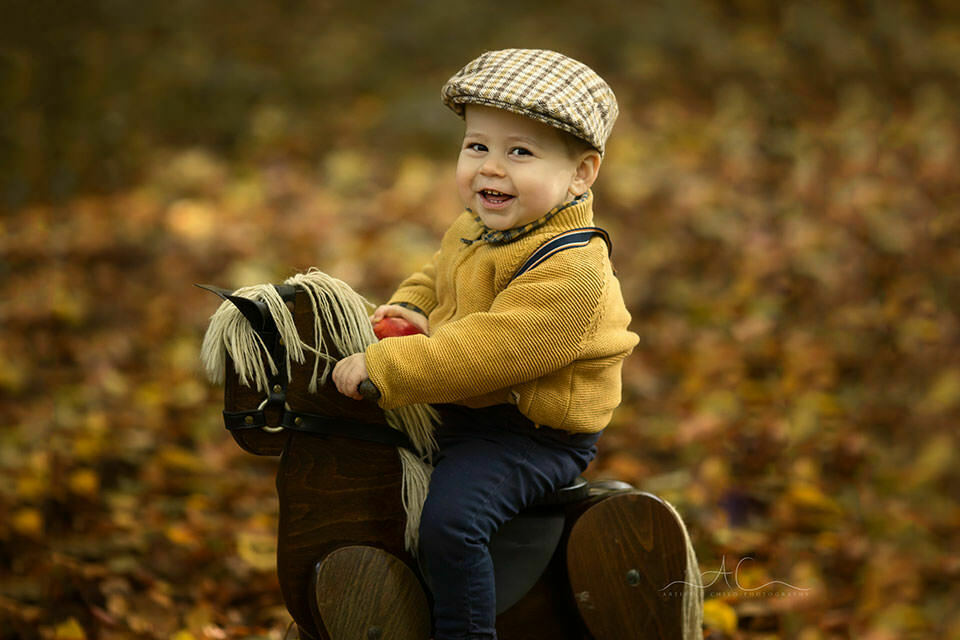 a close up outdoor portrait of a toddler boy laughing while playing with a rocking horse | South East London
