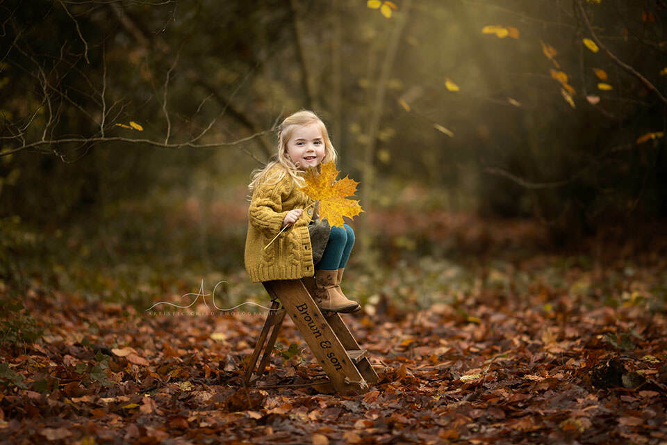 autumnal portrait of a 3 year old girl with a big leaf taken in one of London parks