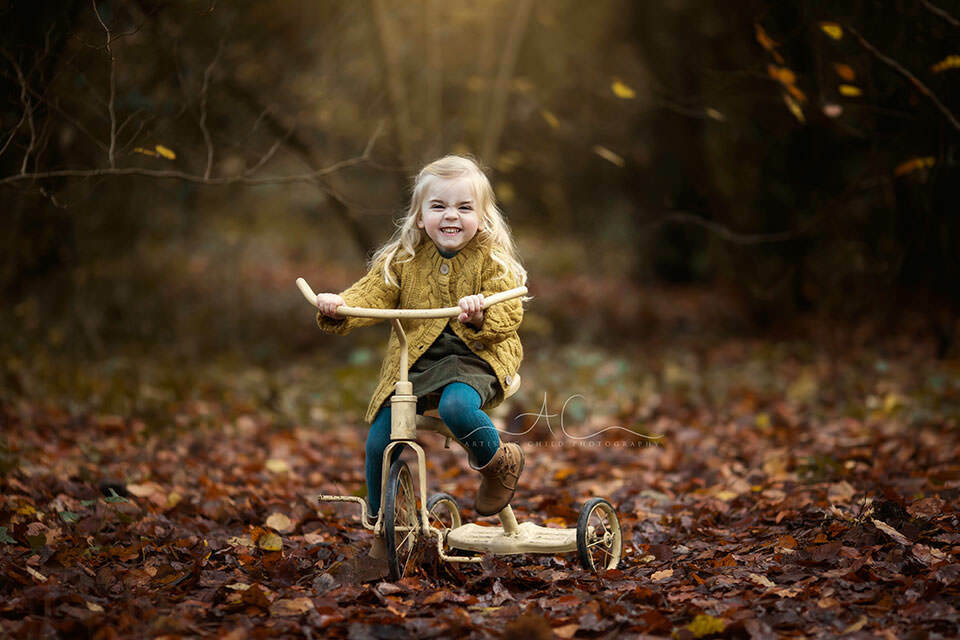 autumnal portrait of a happy 3 year old girl enjoying a ride on an old bike in one of London parks