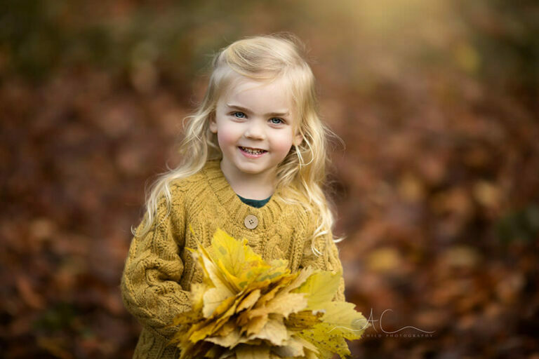 Autumn London Children Photo Session | warm portait of a beautiful 3 year old girl with autumal leafs