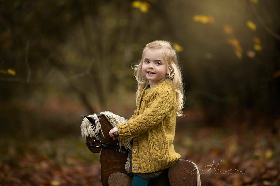 Autumn London Children Photo Session | photo of a 3 year old girl photographed on a rocking horse during autumn season
