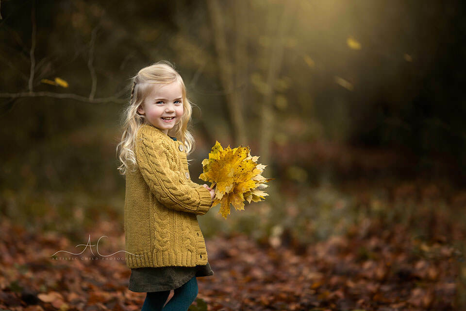 Autumn London Children Photo Session | portrait of a 3 year old girl with big bunch of autumnal leaves