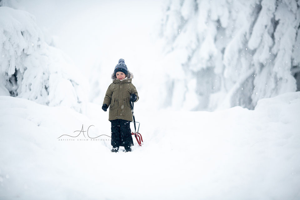 portrait of a 5 year old boy enjoying snow and sledge ride in mountains | London
