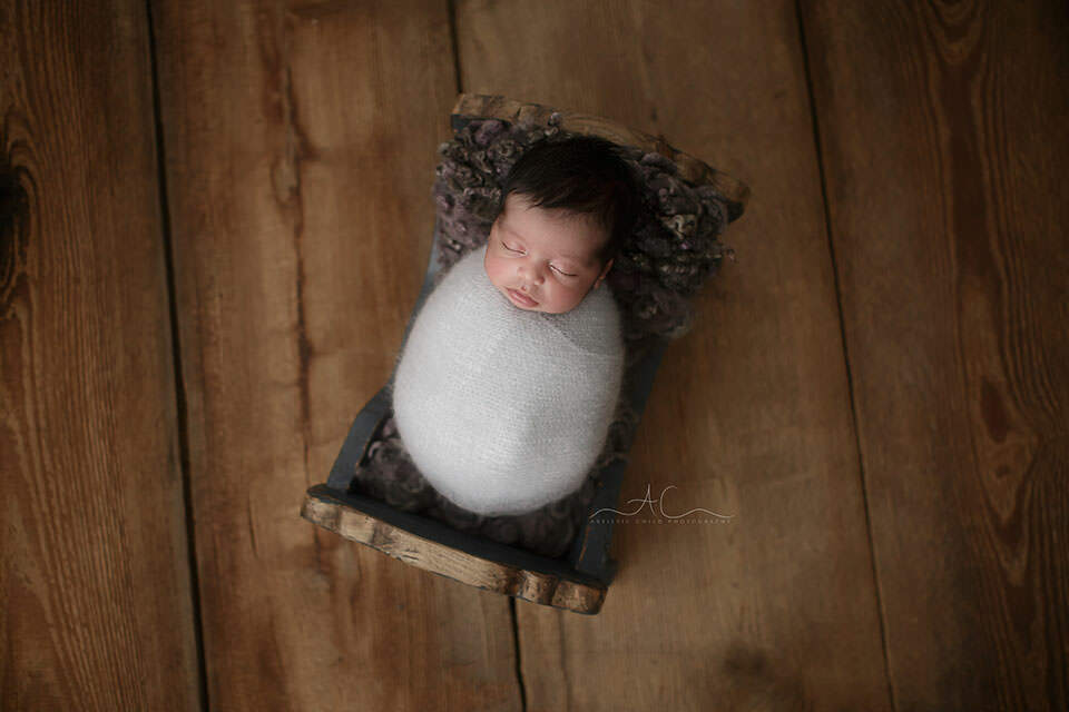 Best London Newborn Photo Session | stunning image of a swaddled newborn baby boy in a blue wooden crate