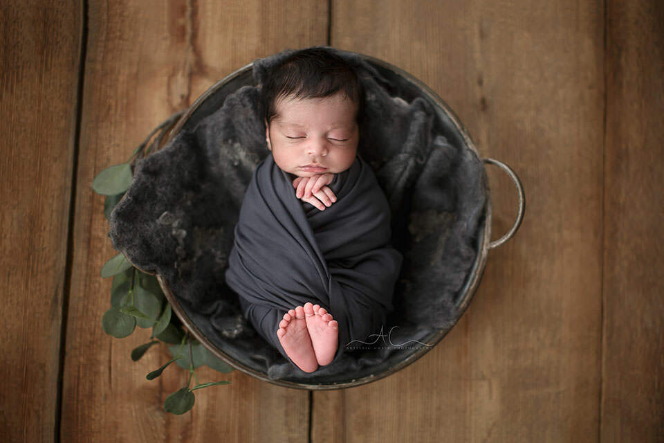 photo of a newborn baby boy swaddled in a grey wrap during a newborn photo session in London