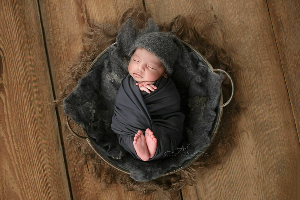 portrait of a newborn baby boy wearing a grey sleeping hat during a newborn photo session in London