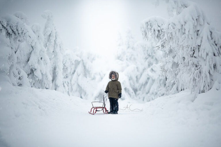 London Children Winter Photo Session | portrait of a 5 year old boy with his sledge walking in mountains full of snow